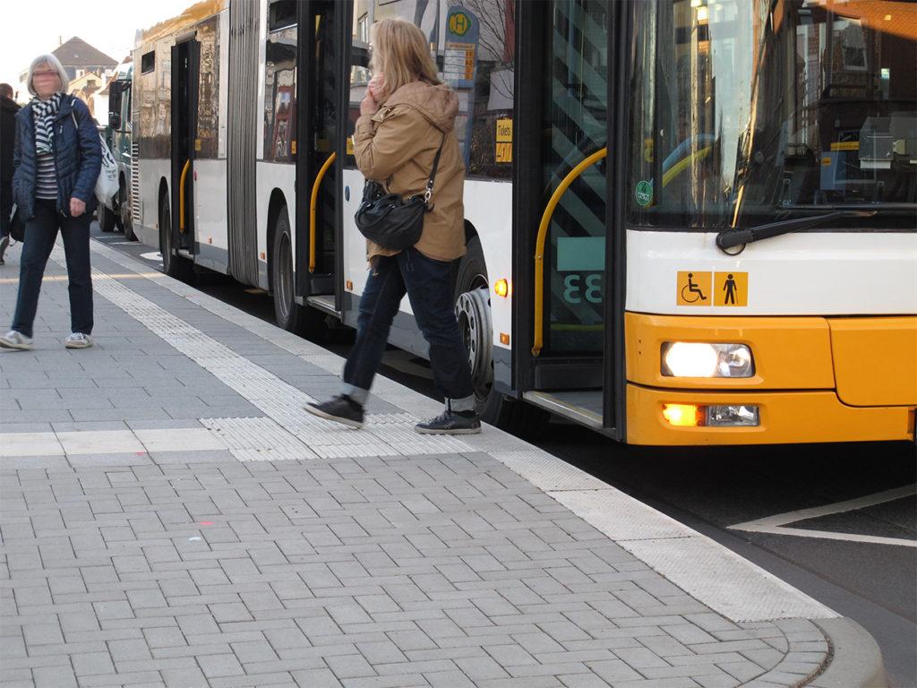 Barrierefrei ausgebaute Haltestelle mit erhöhten Bereich und Leitstreifen für Sehbehinderte. Die Einstiege des Busses liegen höher und es besteht ein deutlicher Spalt zwischen Bordstein und Bus.