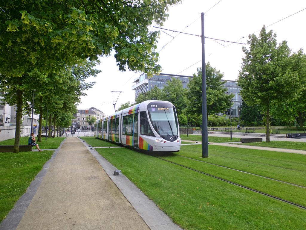Eine Straßenbahn fährt zwischen Bäumen über eine Rasenfläche. Die Rasenfläche erweitert einen Park. Im Hintergrund alte und moderne Gebäude.